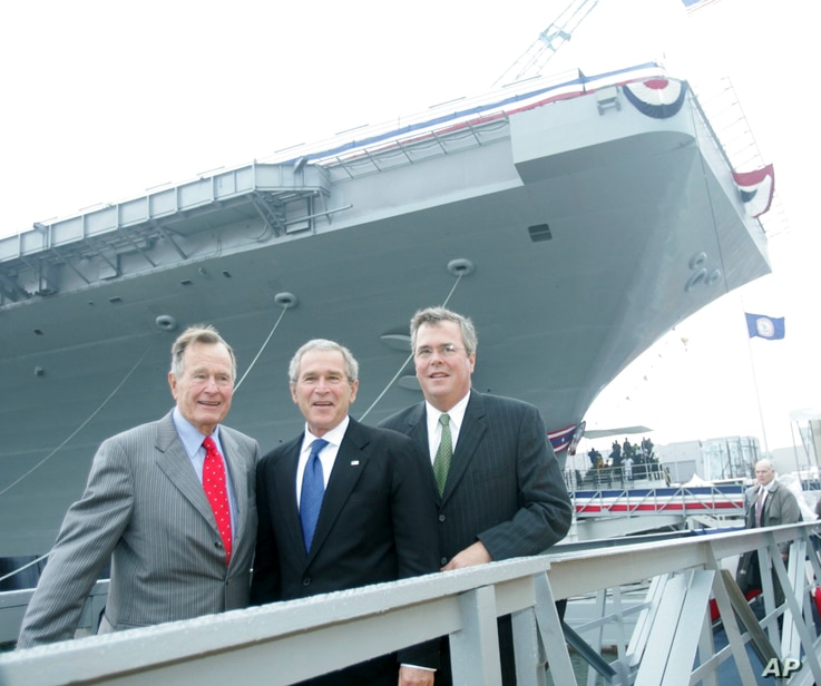 FILE - President George W. Bush, center, with former President George H.W. Bush, left, and Florida Governor Jeb  Bush, right, pose in front of the aircraft carrier George H.W. Bush after participating  in the christening ceremony in Newport News, Va....