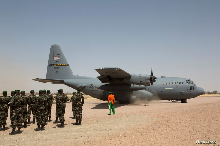 FILE - A C-130 U.S. Air Force plane lands as Nigerien soldiers stand in formation during the Flintlock military exercise in Diffa, Niger, March 8, 2014.