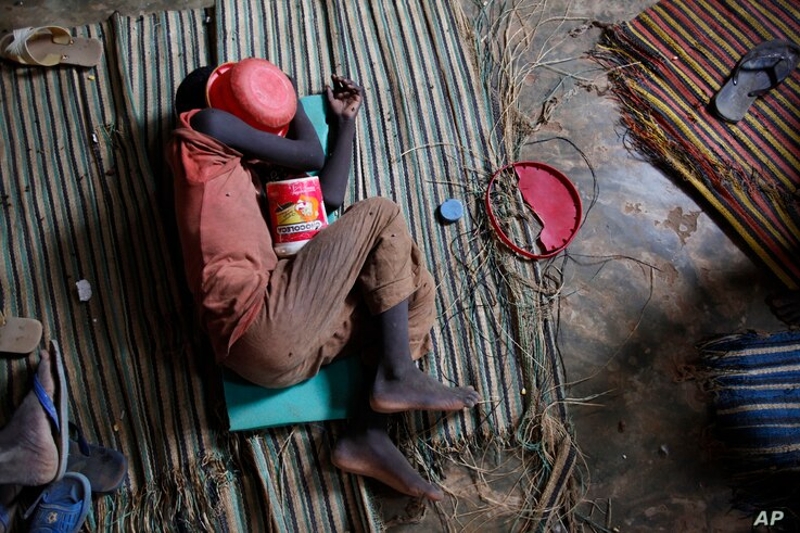 FILE - A Koranic student sleeps with his begging bowl covering his face in the unfinished first floor of a building which serves as both classroom and living space for the dozens of students at his school in Dakar, Senegal, Aug. 31, 2010.