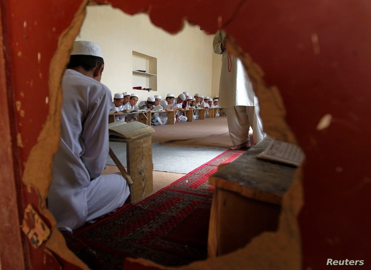 FILE - Boys are seen reading the Koran through a hole in a wall in a madrasa, or religious school, during the Muslim holy month of Ramadan in Kabul, July 26, 2012.