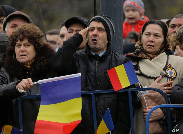 Romanians sing the national anthem during the national day military parade in Bucharest, Dec. 1, 2017.