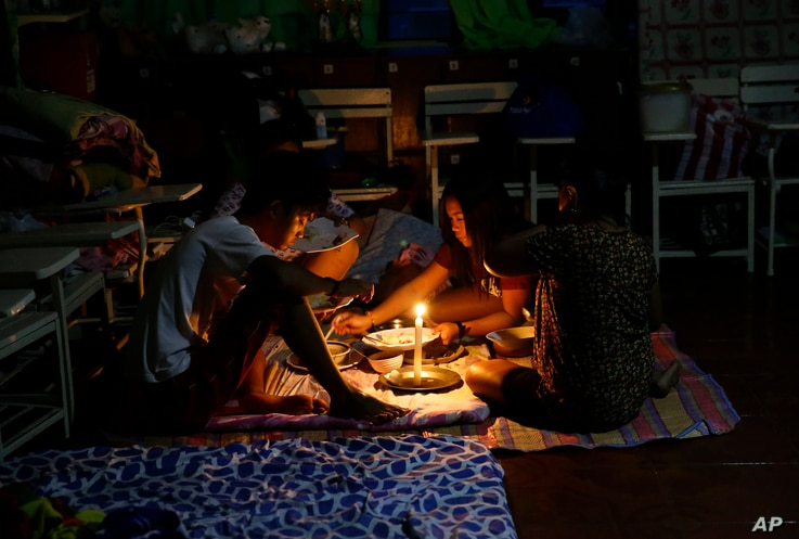 A family shares a meal using a flashlight inside a temporary evacuation center as electricity was shut off following the onslaught of Typhoon Mangkhut in Tuguegarao city in Cagayan province, northeastern Philippines, Sept. 15, 2018.