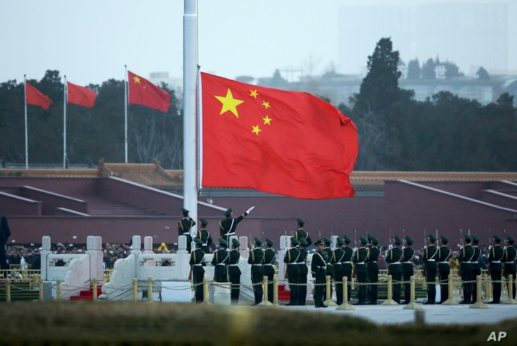 FILE - Chinese paramilitary policemen raise a flag in Tiananmen Square in Beijing, China, March 5, 2016. Improper use of the anthem in China is punishable by up to 15 days in prison.