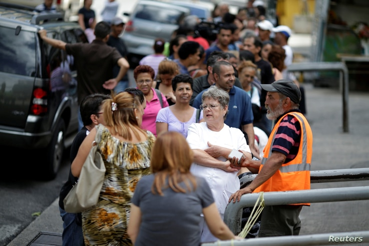 Venezuelan citizens line up to buy food at a store after a strike called to protest against Venezuelan President Nicolas Maduro's government in Caracas, Venezuela, July 29, 2017.