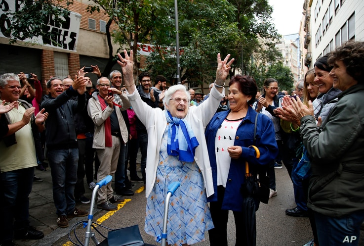 In this Oct. 1, 2017 photo, an elderly lady is applauded as she celebrates after voting at a school assigned to be a polling station in Barcelona, Spain.
