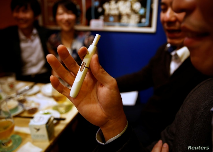 FILE - A man smokes iQOS at a restaurant in Tokyo, Japan, Nov. 2, 2017.