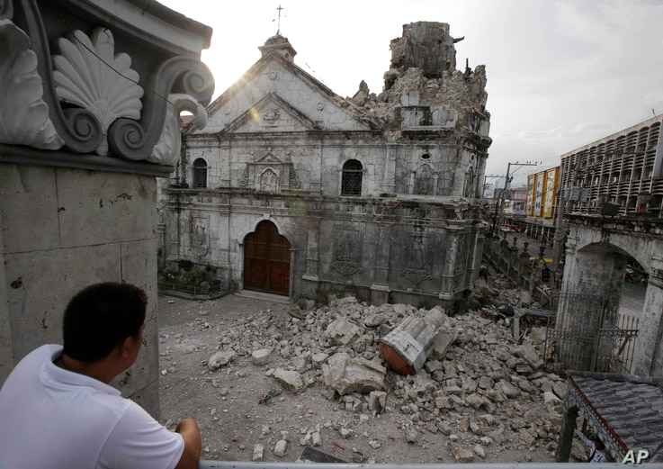 A resident looks at the rubble following an earthquake that hit Cebu city and toppled the bell tower of the Philippines' oldest church, Oct. 15, 2013.