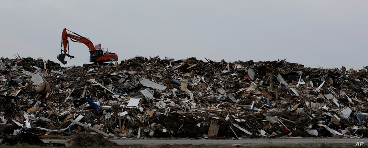 An excavator is used to move a mountain of debris created in the wake of Hurricane Harvey, Port Aransas, Texas, Sept. 29, 2017.