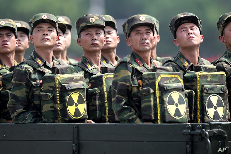 FILE - In this July 27, 2013, file photo, North Korean soldiers carrying packs marked with the nuclear symbol turn and look towards leader Kim Jong Un during a military parade in Pyongyang, North Korea.