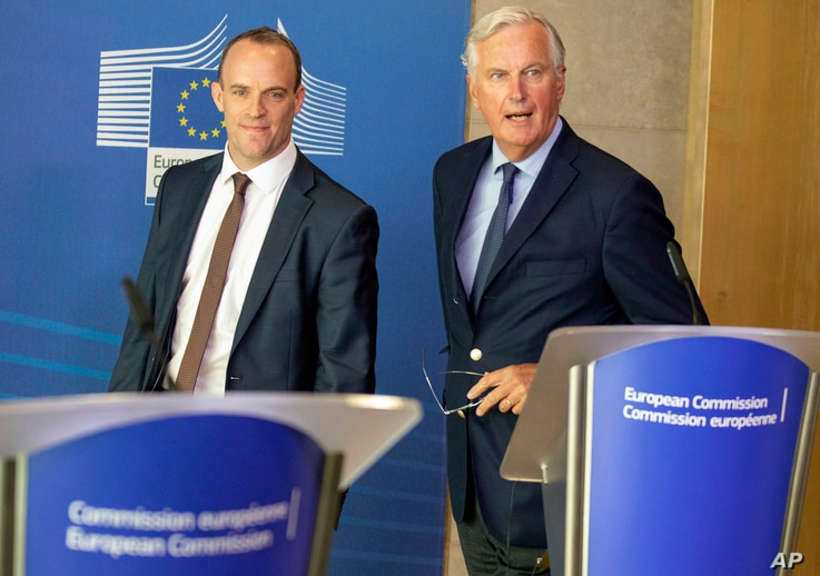 Britain's Secretary of State for Exiting the European Union Dominic Raab, left, and EU chief Brexit negotiator Michel Barnier arrive for a press conference at EU headquarters in Brussels, Aug. 21, 2018.