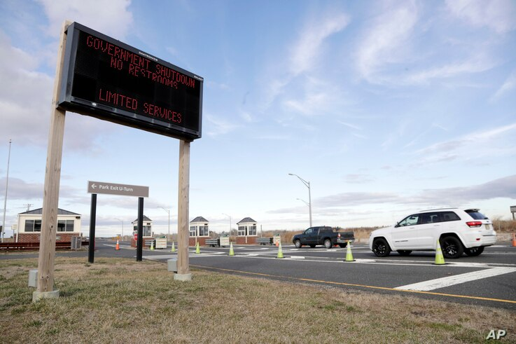 FILE - Vehicles roll into the Gateway National Recreation Area-Sandy Hook near a sign at the entrance warning visitors of limited services such as closed restrooms during the partial government shutdown in Highlands, N.J., Jan. 3, 2019.