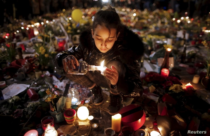 A girl lights candles as people pay tribute to the victims of Tuesday's bomb attacks, at the Place de la Bourse in Brussels, Belgium, March 26, 2016.