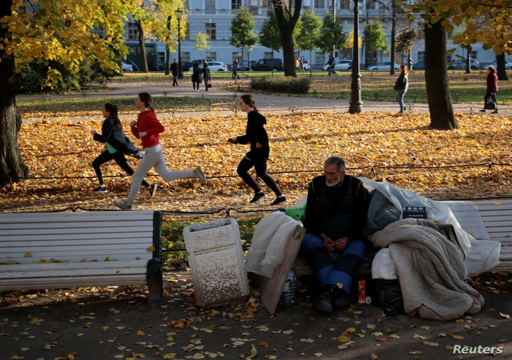 FILE - Youths train behind a homeless man sitting on a bench at the Alexander Garden on a sunny autumn day in St. Petersburg, Russia, Oct. 16, 2018.