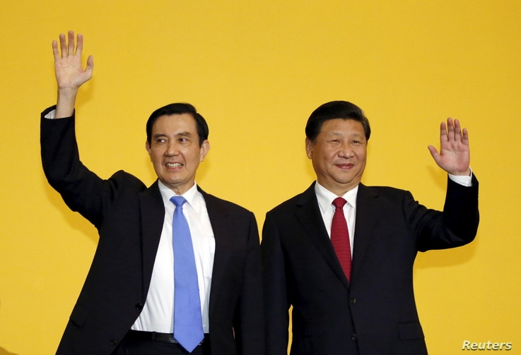 Chinese President Xi Jinping and Taiwan's President Ma Ying-jeou, left, wave to the media during a summit in Singapore, Nov. 7, 2015.
