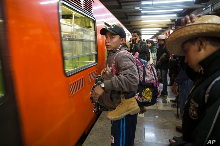Central American migrants stand waiting for a subway car after leaving the temporary shelter in the Jesus Martinez stadium, in Mexico City, Nov. 9, 2018.