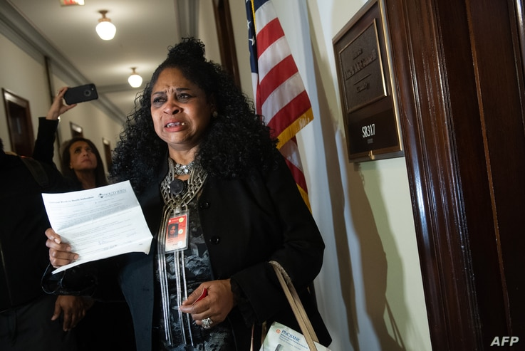 Faye Smith, a furloughed Smithsonian contract worker who has not been paid during the partial government shutdown, holds an unpaid electric bill to present to Senate Majority Leader Mitch McConnell's office on Capitol Hill in Washington, DC, Jan. 16,...