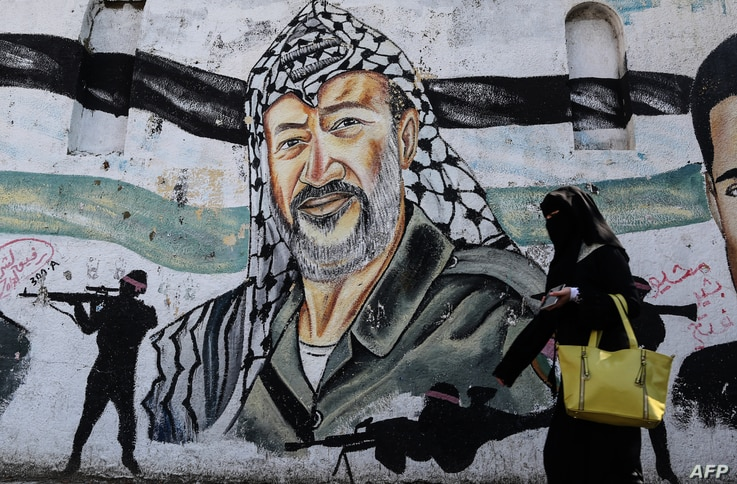 A veiled Palestinian woman walks past a mural on a wall depicting late Palestinian leader Yasser Arafat as Palestinians mark the 14th anniversary of Arafat's death, in Gaza City, Nov. 11, 2018.