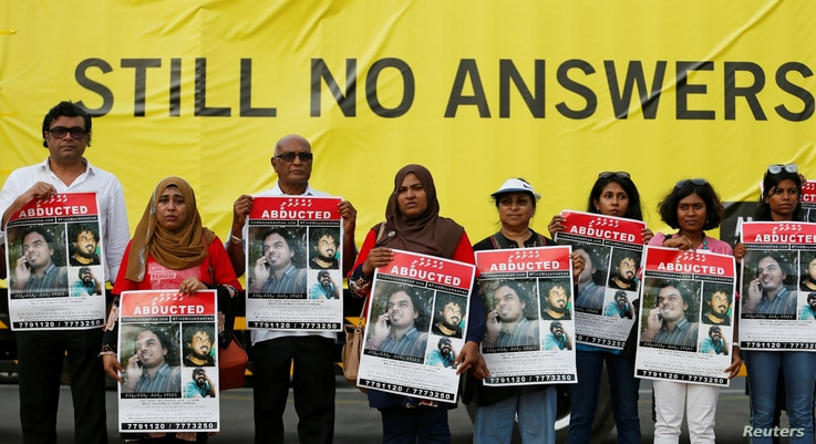 """A group of Maldivians hold posters of disappeared Maldivian journalist Ahmed Rilwan Abdulla as they mark the """"International Day of the Disappeared"""" in Colombo, Sri Lanka, Aug. 28, 2018."""