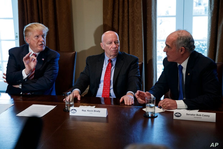 Rep. Kevin Brady, R-Texas, center, listens as President Donald Trump speaks to Sen. Bob Casey, D-Pa., during a meeting with lawmakers about trade policy in the Cabinet Room of the White House, Feb. 13, 2018.