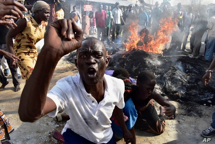 A opposition supporter reacts after burning tyres during demonstrations in Mombasa, Kenya, Oct. 26, 2017.
