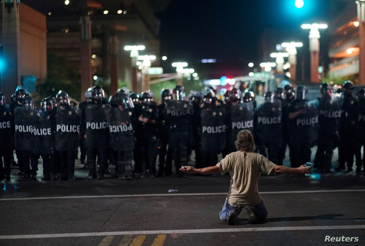 A demonstrator taunts Police officials after a Donald Trump campaign rally in Phoenix, Arizona, U.S. August 22, 2017.