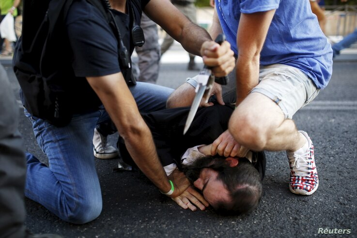 People disarm an Orthodox Jewish assailant shortly after he stabbed participants at the annual Gay Pride parade in Jerusalem July 30, 2015. The man stabbed and wounded six participants during the march on Thursday, police said.