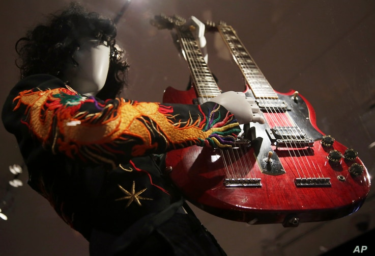"""A double-neck guitar played by Jimmy Page of Led Zeppelin is displayed at the exhibit """"Play It Loud: Instruments of Rock & Roll,"""" at the Metropolitan Museum of Art in New York, April 1, 2019."""