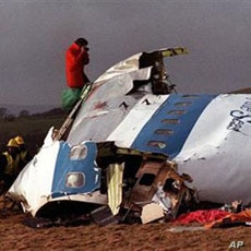 Police and investigators look at what remains of the flight deck of Pan Am 103 on a field in Lockerbie, Scotland, December 22, 1988 file photo