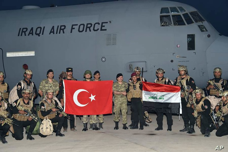Turkish and Iraqi soldiers hold their national flags after the arrival of Iraqis in Silopi, near the Habur border gate with Iraq, southeastern Turkey, Sept. 25, 2017.