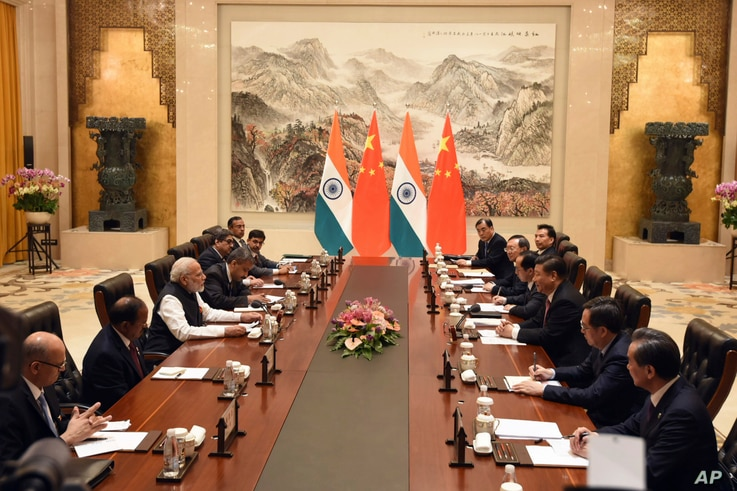In this photo released by the Indian Ministry of External Affairs, Indian Prime Minister Narendra Modi, center left, and Chinese President Xi Jinping, center right, sit with delegation members for a meeting in Wuhan, China, Friday, April 27, 2018.