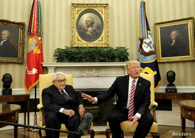 With former Secretary of State Henry Kissinger (L) at his side, U.S. President Donald Trump speaks to reporters