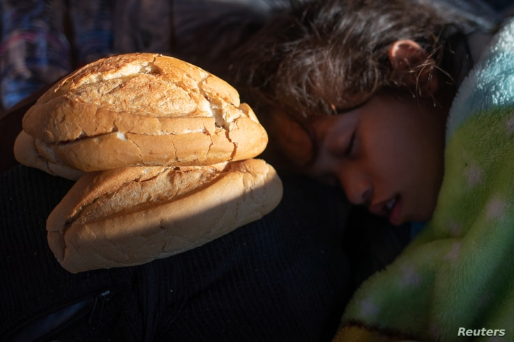 A girl, part of a caravan of thousands of migrants from Central America en route to the United States, sleeps next to bread donated by a passer-by in Tapachula, Mexico, Oct. 22, 2018.