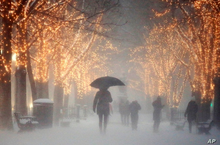 People walk through the Commonwealth Avenue Mall during a winter storm in Boston, Jan. 7, 2017. A storm that wreaked havoc along the East Coast arrived in southern New England Saturday, bringing blizzard conditions to some areas and making travel tre...