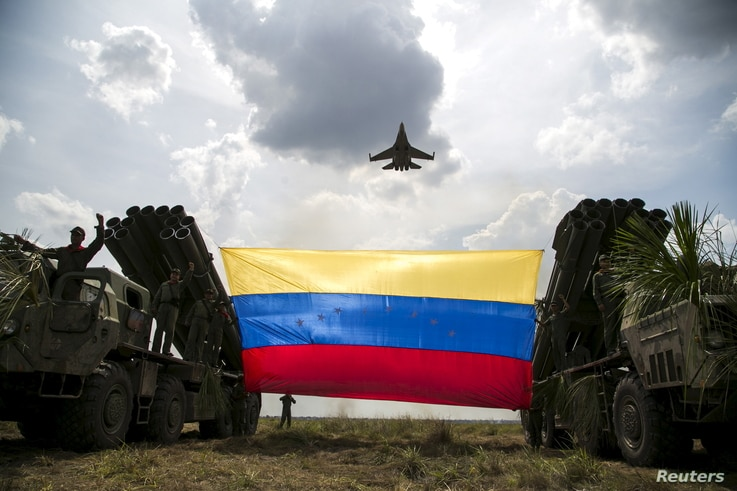 """A Russian-made Sukhoi Su-30MKV fighter jet of the Venezuelan Air Force flies over a Venezuelan flag tied to missile launchers, during the """"Escudo Soberano 2015"""" (Sovereign Shield 2015) military exercise in San Carlos del Meta in the state of Apure Ap"""