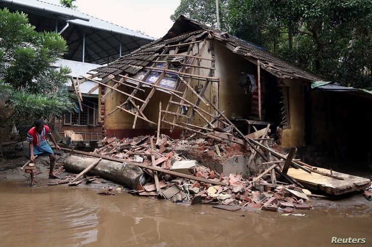 A man removes debris from a collapsed house after floods in Paravur, in the southern state of Kerala, India, Aug. 23, 2018.