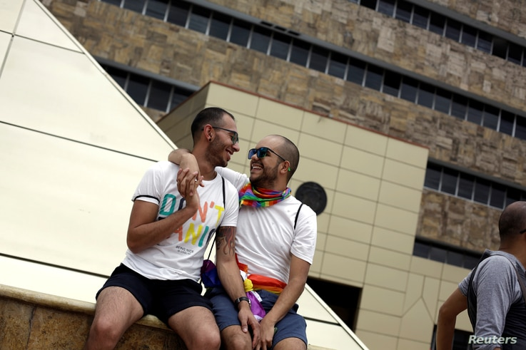 A gay couple takes part of a concentration of LGBT community members and activists in front of the Supreme Court of Justice, to demand constitutional magistrates to give a positive ruling on equal marriage in San Jose, Costa Rica, Aug. 4, 2018.