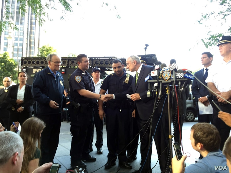 New York City Police Commissioner Bill Bratton greets Sgt. Hameed Armani, right, and Officer Peter Cybulski at a news conference at Columbus Circle in New York, Thursday, July 21, 2016.