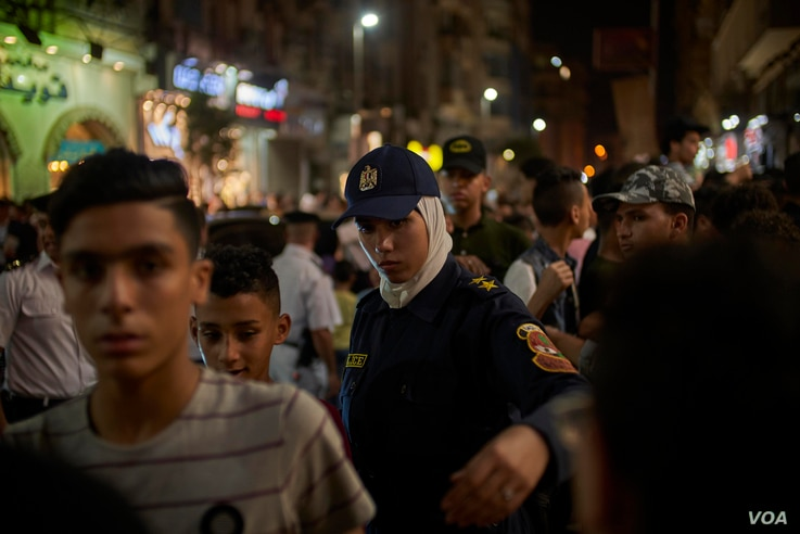 Policewomen show up on duty at movie theaters to organize crowds and protect girls from possible sexual harassment in downtown Cairo, Egypt on Friday, June 15, 2018.