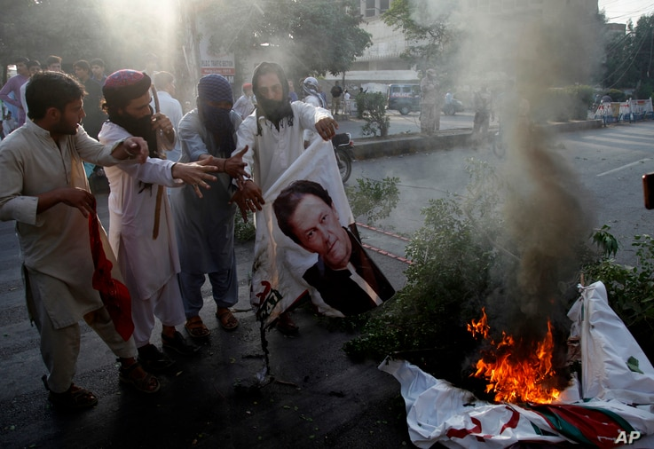 FILE - Supporters of Pakistani radical groups burn a poster of Pakistani Prime Minister Imran Khan during a rally to condemn a Supreme Court decision that acquitted Asia Bibi, a Christian woman, who spent eight years on death row accused of blasphemy...