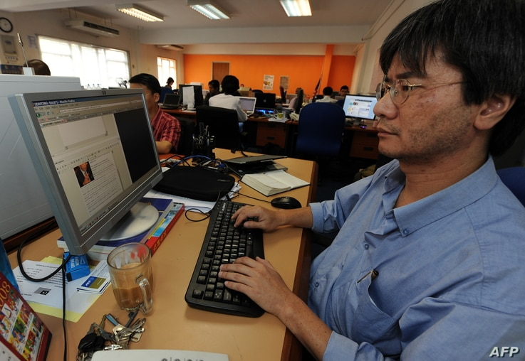 FILE - Steven Gan (R), one of the founder of a news website Malaysiakini, works on a story in his office in Kuala Lumpur on November 20, 2008.