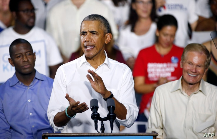 Florida Democratic gubernatorial nominee Andrew Gillum (L), and Senator Bill Nelson (D-FL) (R) listen to former President Barack Obama as he addresses the media and supporters as they stump for votes at a rally in Miami, Florida