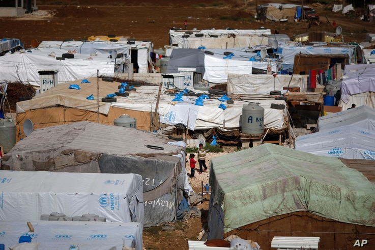 FILE - Syrian refugees stand outside their tents at a Syrian refugee camp in the town of Hosh Hareem, in the Bekaa valley, east Lebanon, Oct. 28, 2015.