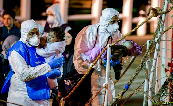 Rescuers help children disembark in the Sicilian harbor of Pozzallo, Italy, April 20, 2015. About 100 migrants, including 28 children, were rescued on Sunday by a merchant vessel in the Sicilian Strait while they were trying to cross.