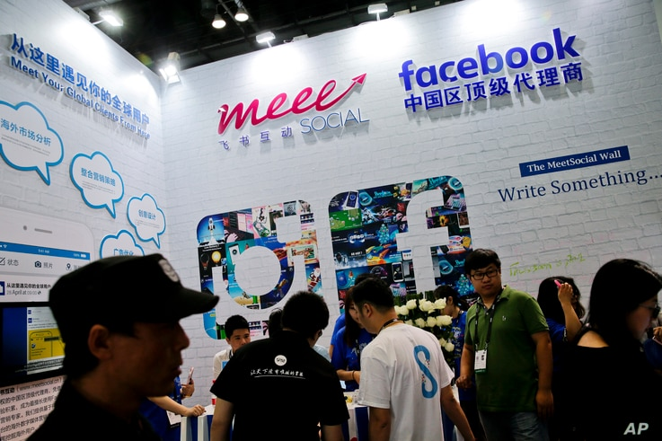 FILE - visitors gather at a social network company booth which enable people to connect global clients during the 2016 Global Mobile Internet Conference (GMIC) in Beijing.