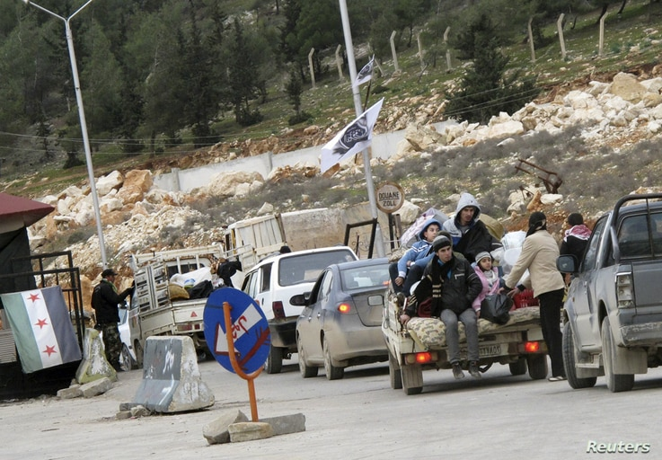 Syrian refugees wait to cross the border to Turkey at Bab El-Hawa on the outskirts of Idlib, January 13, 2013.