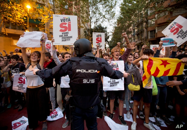 A Spanish national police officer tries to stop demonstrators protesting outside the main offices of the left wing party CUP in Barcelona, Spain, Sept. 20, 2017.