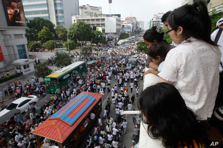 FILE - People watch the funeral procession of Cambodian leading government critic Kem Ley in Phnom Penh, Cambodia, July 24, 2016.