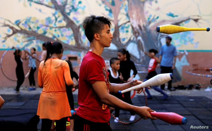 "A boy performs during a training session at al-Darb al-Ahmar Arts School ""DAAS"" where children learn circus skills and arts in old Cairo, Egypt, July 17, 2018."