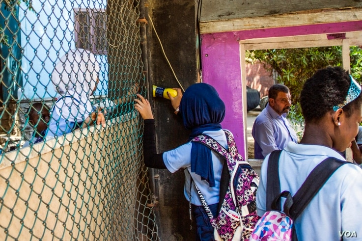 A school girl passes a bottle of juice to her colleague from the street before classes start Sept. 16, 2017, at the African Hope School in Cairo, Egypt.