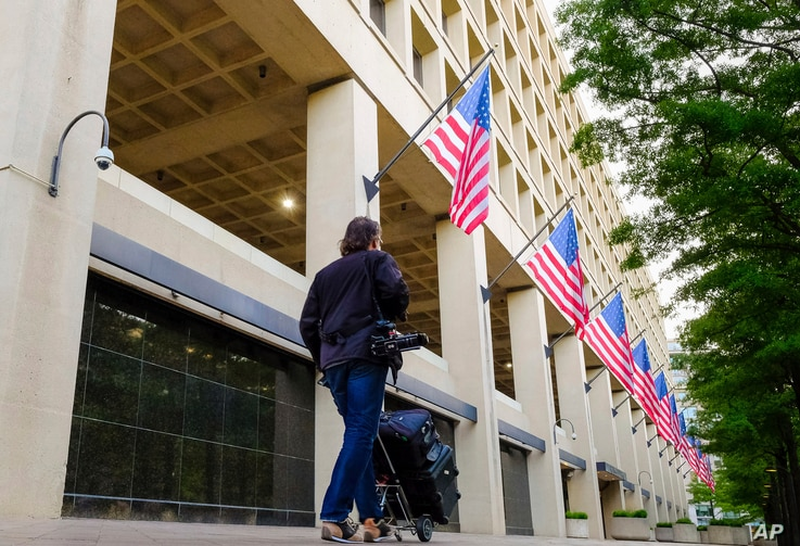 A member of the news media walks in front of the FBI headquarters building early in the morning in Washington, May 10, 2017. President Donald Trump fired FBI Director James Comey Tuesday evening.